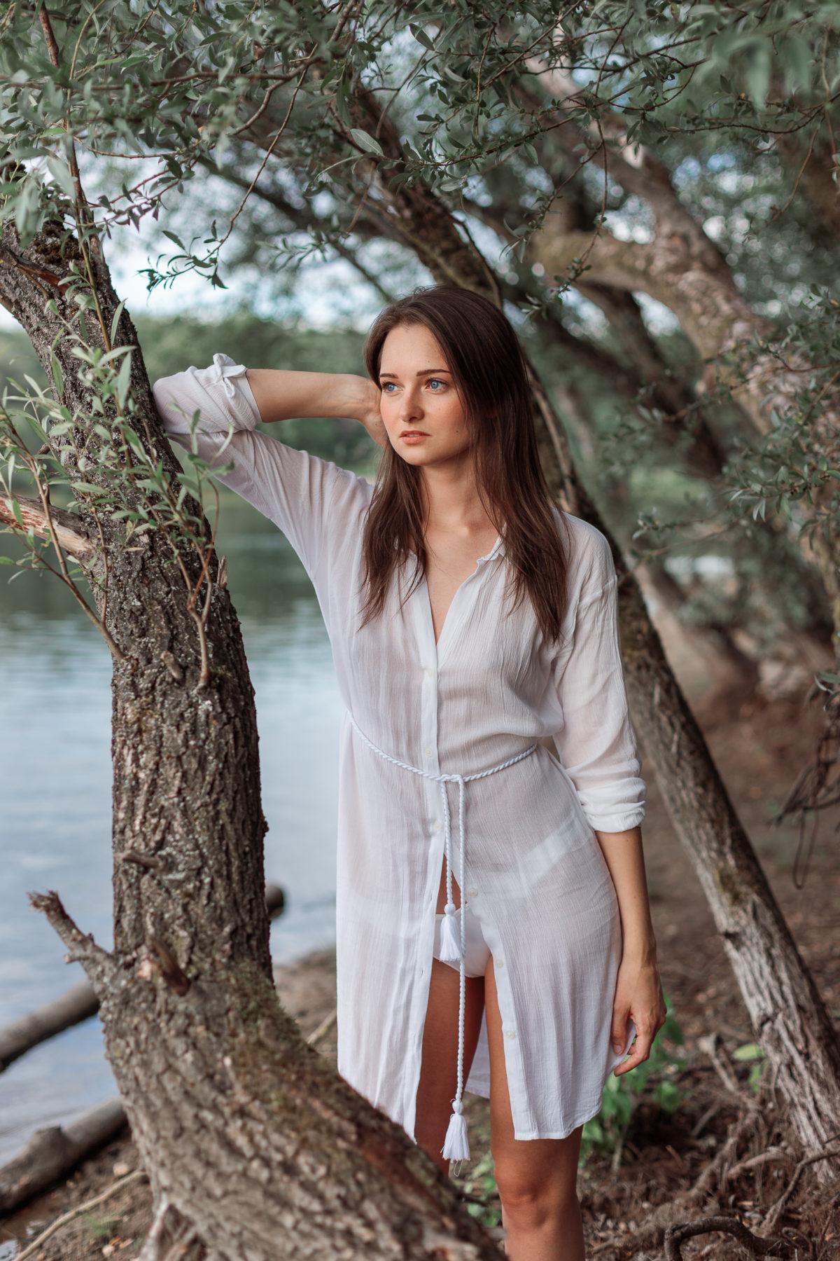 Frau zwischen Bäumen am See
